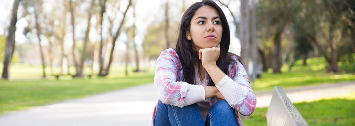 A Hispanic woman sitting on top of a bench in a park contemplating holding up her head with her hand