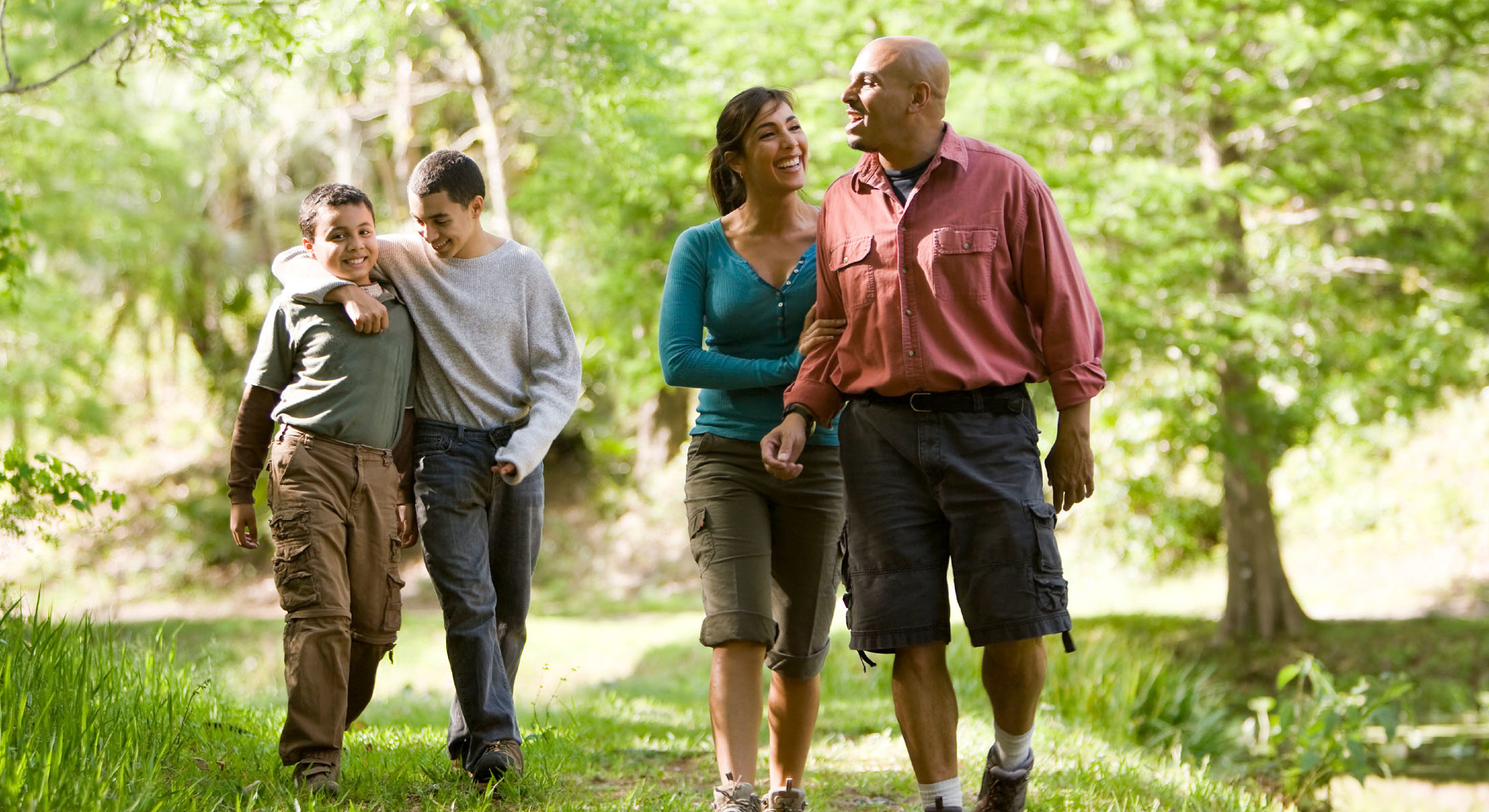 Hispanic family walking outdoors smiling with two sons